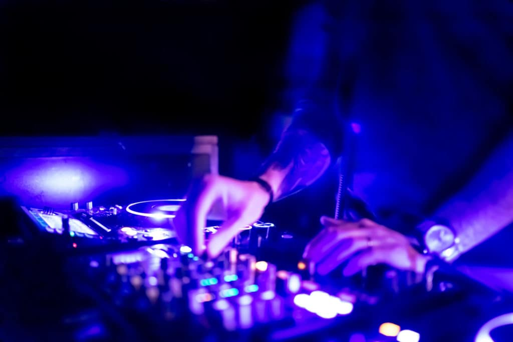 a dj uses knobs to adjust the equalization of the songs he is plying.